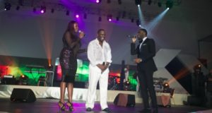 Waje, Jonny Gills and Praiz performing together on stage.