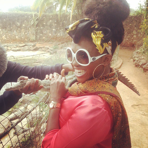 Waje having fun with a baby crocodile
